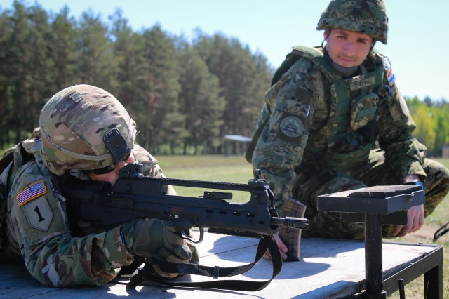 "Croatian army 1st Lt. Zoran Glubovic (right), assigned to Croatian ""Storm"" Artillery Rocket Battery, gives ammunition to Sgt. 1st Class Martha Pagan (left), career counselor assigned to 1st Squadron, 2nd Cavalry Regiment, before firing the Produkt VHS assault rifle during a multinational weapons range with Battle Group Poland at Bemowo Piskie Training Area, Poland, on May 8, 2018."