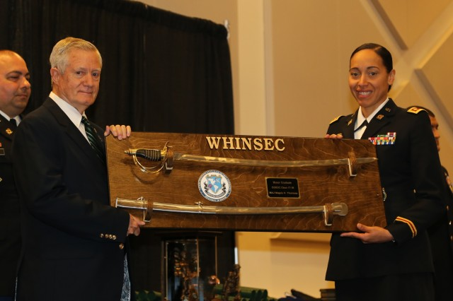 Major Magaly Thurman, the U.S. Distinguished Graduate, shares a moment with Lt. Col. (Ret) Mayo (Biff) Hadden as he presents the saber donated by Chapter 59, Special Forces Association.  She also earned a Master of Military Arts and Science during her year at the Institute.