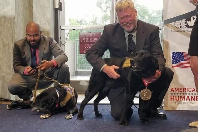 Retired Army Sgt. Dennis Dow, right, pets former military working dog Jag moments after Jag received the Lois Pope K-9 Medal of Courage in Washington, D.C., May 22, 2018.
