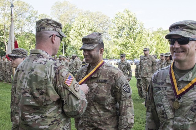 U.S. Army Maj. Navin Kalicharan, operations officer of the 369th Sustainment Brigade, New York Army National Guard, is presented the Shield of Saint Christopher by Col. Stephen Bousquet, commander of the 369th Sustainment Brigade, during a ceremony at Camp Smith, N.Y., June 2, 2018. The Military Order of Saint Christopher recognizes those individuals who have made significant contributions to the U.S. Army Transportation Corps. (U.S. Army National Guard photo by Sgt. Jeremy Bratt)