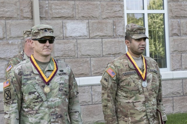U.S. Army Lt. Col. Shawn J. Shutts, deputy commander of the 369th Sustainment Brigade (SB), and Maj. Navin Kalicharan, operations officer of the 369th SB, New York Army National Guard, are presented the Shield of Saint Christopher by Col. Stephen Bousquet, commander of the 369th SB, during a ceremony at Camp Smith, N.Y., June 2, 2018. The Military Order of Saint Christopher recognizes those individuals who have made significant contributions to the U.S. Army Transportation Corps. (U.S. Army National Guard photo by Sgt. Jeremy Bratt)