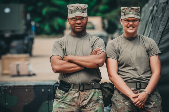 Pfc. Roffes Watson and Pfc. Renee Shaw stand next the the field showers at their forward operating base during Saber Strike 18, June 1, 2018. Pfc. Watson and Pfc. Shaw will be performing field shower and laundry support with the 464th Quartermaster Company during Saber Strike 18.