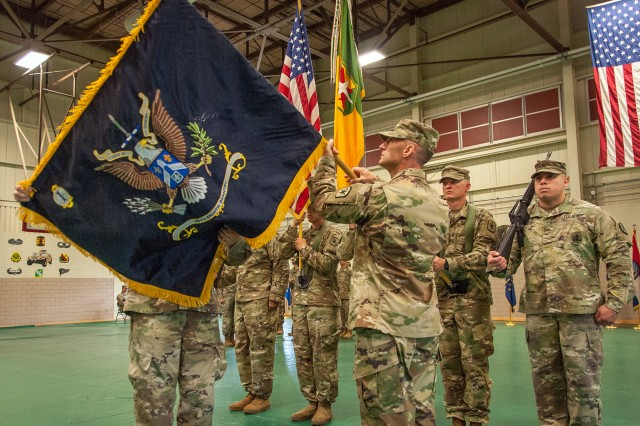 Col. Curtis Schroeder, 14th Military Police Brigade commander, right, and Commander Sgt. Maj. Anthony Rodriques unfurl the colors for the 1st Battalion, 58th Infantry Regiment, during the battalion activation ceremony May 24.