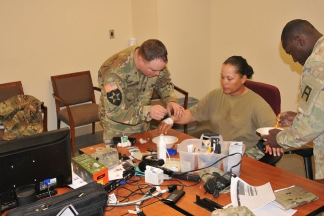 Sgt. 1st Class Jessica Douglas (center) works with other First Army Soldiers during a moulage class while supporting the 155th Armored Brigade Combat Team's mobilization and validation exercise at Fort Bliss, Texas. Douglas, who is self-taught, used her k knowledge to provide insight and training to other OC/Ts to enhance the realism of potential wounds suffered on the battlefield. (Photo Credit: 177th Armored Brigade Public Affairs)