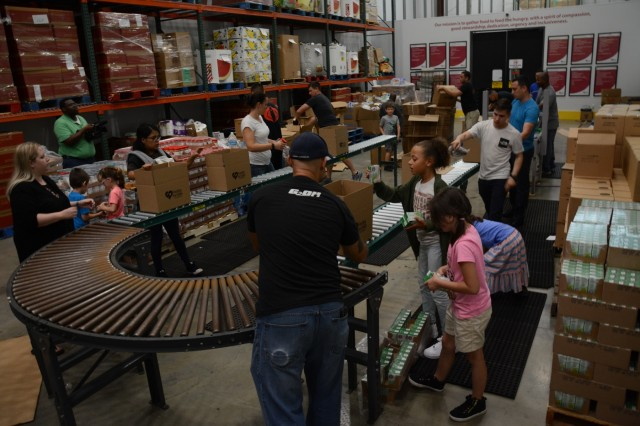 Soldiers of Charlie Company, 1st Battalion, 46th Infantry Regiment, at Fort Benning, Georgia, and their Family members, pack boxes of food June 1 at the Feeding the Valley Food Bank in Midland, Georgia, during a community service project. The food bank is one of eight regional food banks in Georgia and is the centralized source for receiving and distributing donated food, produce and grocery products to families in need. (U.S. Army photo by Megan Garcia, Maneuver Center of Excellence, Fort Benning Public Affairs)