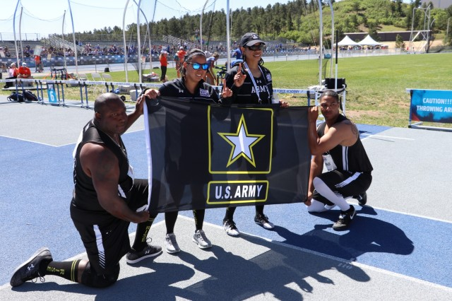 Team Army members, from left, U.S Army Staff Sgt. Dorian Rhoten, Sgt. 1st Class Hyoshin Cha, Staff Sgt. Altermese Kendrick, and Sgt. Samuel Daniels display the team flag after competing in the discus event, June 2, 2018, at the U.S. Air Force Academy outdoor track facility during the 2018 Department of Defense Warrior Games, June 2 - 9. The DoD Warrior Games is an adaptive sports competition for wounded, ill and injured service members and veterans. Approximately 300 athletes representing teams from the Army, Marine Corps, Navy, Air Force, Special Operations Command, United Kingdom Armed Forces, Canadian Armed Forces, and the Australian Defence Force will compete in archery, cycling, track, field, shooting, sitting volleyball, swimming, wheelchair basketball, and - new this year - powerlifting and indoor rowing. (U.S. Army photo by Robert Whetstone)