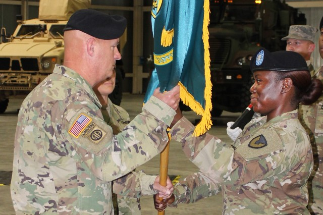 Lt. Col. Crystal Hills, outgoing commander, Army Field Support Battalion--Africa, passes the battalion colors to Col. Rodney H. Honeycutt, 405th AFSB commander, at a change of command ceremony June 1 at Leghorn Army Depot in Livorno, Italy.