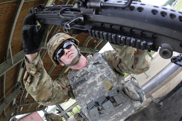 Pfc. Brian Fitzgerald, 508th Transportation Company, 266th Quartermaster Battalion, assembles a M240B machine gun during the assemble/disassemble portion of the Ultimate Warrior Competition May 22 at the range training complex. Fitzgerald was competing in the Soldier of the year category.