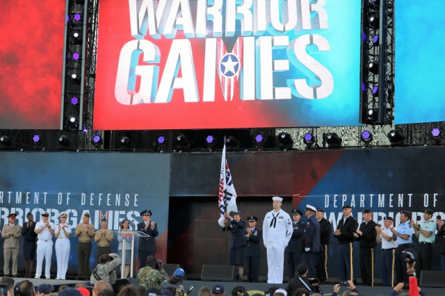 Senior leaders from all U.S. armed services were on hand as U.S. Air Force Lt. Gen. Gina Grosso, Deputy Chief of Staff for Manpower, Personnel and Services, unfurls for the first time the official colors of the Warrior Games during the opening ceremony, June 2, 2018, at the U.S. Air Force Academy's Falcon Stadium at the 2018 Department of Defense Warrior Games, June 2 - 9. The DoD Warrior Games is an adaptive sports competition for wounded, ill and injured service members and veterans. Approximately 300 athletes representing teams from the Army, Marine Corps, Navy, Air Force, Special Operations Command, United Kingdom Armed Forces, Canadian Armed Forces, and the Australian Defence Force will compete in archery, cycling, track, field, shooting, sitting volleyball, swimming, wheelchair basketball, and - new this year - powerlifting and indoor rowing. (U.S. Army photo by Robert Whetstone)