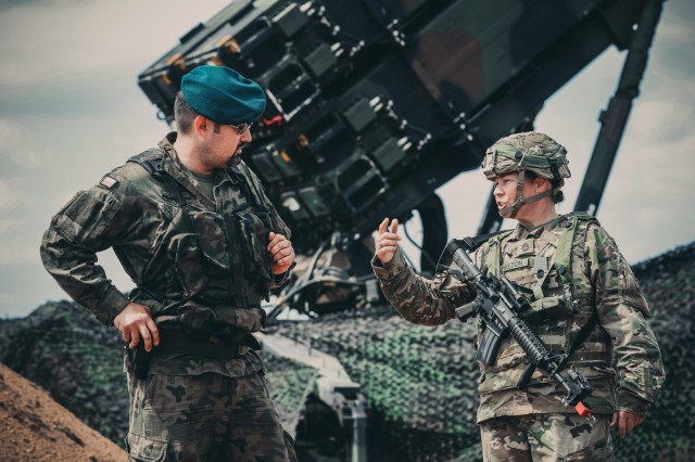Cpt. Grzegorz Piskiewcz, the air defense officer, 12th Mechanized Division Headquarters, and Sgt. 1st Class Paige Shelton from the 5th Battalion, 7th Air Defense Artillery Regiment, discuss some of the capabilities of the new U.S. Army patriot missile system in the Drawsko Pomorskie area of Poland, June 4, 2018. Educating our allies on our defense strategies and weapon systems builds confidence among our multinational partners across the globe.
