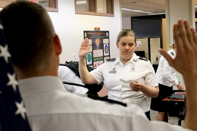 Capt. (Dr.) Lindsay Grubish administers the oath of office to new physicians arriving for their graduate medical education June 1 at Madigan Army Medical Center on Joint Base Lewis-McChord, Washington. Grubish is the officer-in-charge for the interns and serves as their core curriculum director. This year's class has 71 physicians.