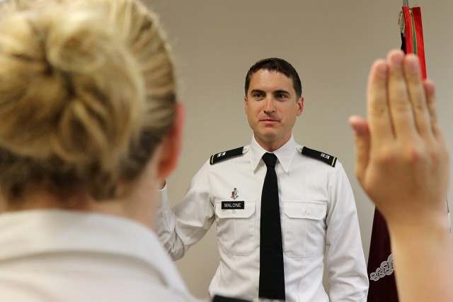 Capt. (Dr.) John Malone takes the oath of office June 1 from Capt. (Dr.) Lindsay Grubish, the officer-in-charge for the incoming class of 71 physicians receiving their graduate medical education at Madigan Army Medical Center on Joint Base Lewis-McChord, Washington.