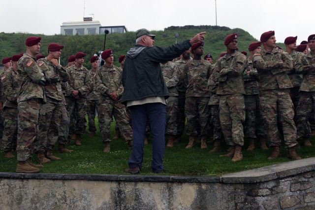 Col. (ret) Keith Nightingale (center), a former 82nd Airborne Division battalion commander and paratrooper, recounts historical facts to current 82nd Abn. Div. paratroopers during a staff ride on May 31, at Normandy, France. Nightengale toured the paratroopers to Omaha Beach and recounted the D-Day invasion to the group.