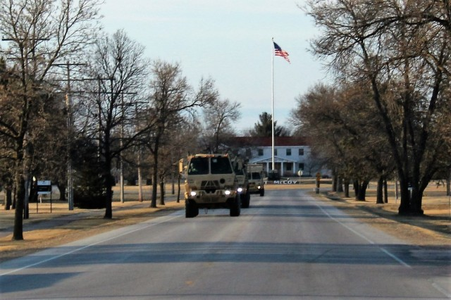 Military trucks move in a convoy at the installation March 28, 2018, in the late evening while the American flag can be seen flying on the garrison flagpole in from of Garrison Headquarters at Fort McCoy, Wis. The trucks and the Soldiers operating them were part of the Operation Cold Steel II exercise taking place at Fort McCoy. (U.S. Army Photo by Scott T. Sturkol, Public Affairs Office, Fort McCoy, Wis.)
