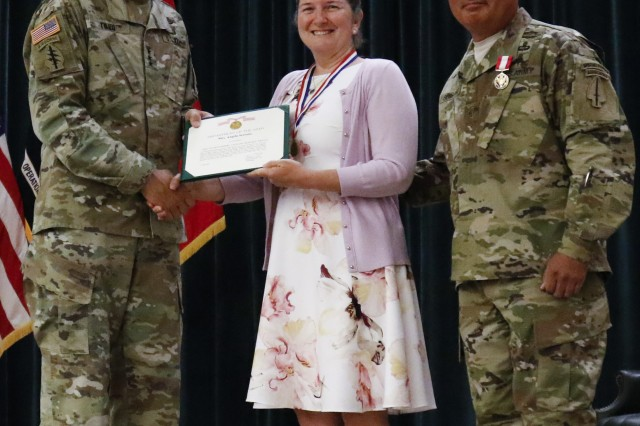 Lt. Gen. Kenneth E. Tovo, U.S. Army Special Operations Command commander, presents the Outstanding Civilian Award to Angela Serrano during a ceremony honoring her husband, Chief Warrant Officer 5 Heriberto Serrano Jr., Fort Bragg, June 1, 2018.