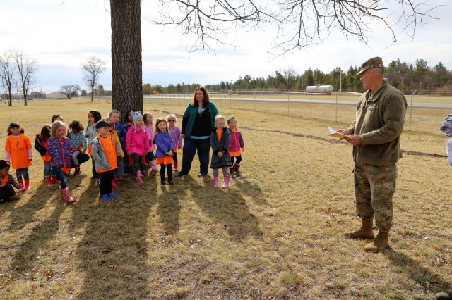 Garrison Commander Col. David J. Pinter Sr. reads the children's proclamation with students and staff with the Child Development Center during an Arbor Day observance April 27, 2018, at Fort McCoy, Wis. Dozens of adults and children from the Fort McCoy community participated in the installation's 30th observance of Arbor Day with the planting of more than 400 trees on the cantonment area. The installation ceremony included not only the planting of 415 trees, but also the reading of the Arbor Day proclamation and the presentation of the installation's 29th consecutive Tree City USA award. (U.S. Army Photo by Scott T. Sturkol, Public Affairs Office, Fort McCoy, Wis.)