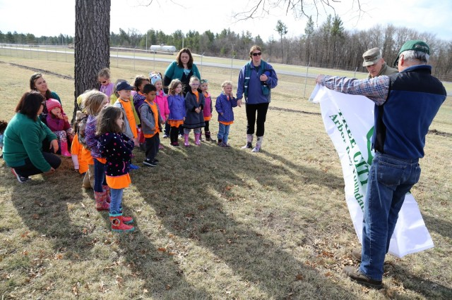 Forester James Kerkman with the Forestry Office of the Directorate of Public Works Environmental Division Natural Resources Branch shows students and staff with the Child Development Center and others a new Tree City USA flag during an Arbor Day observance April 27, 2018, at Fort McCoy, Wis. Dozens of adults and children from the Fort McCoy community participated in the installation's 30th observance of Arbor Day with the planting of more than 400 trees on the cantonment area. The installation ceremony included not only the planting of 415 trees, but also the reading of the Arbor Day proclamation and the presentation of the installation's 29th consecutive Tree City USA award. (U.S. Army Photo by Scott T. Sturkol, Public Affairs Office, Fort McCoy, Wis.)
