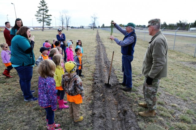 Forester James Kerkman shows how to plant a tree on April 27, 2018, with students and staff with the Child Development Center and others during the Fort McCoy, Wis., observance of Arbor Day. Dozens of adults and children from the Fort McCoy community participated in the installation's 30th observance of Arbor Day with the planting of more than 400 trees on the cantonment area. The installation ceremony included not only the planting of 415 trees, but also the reading of the Arbor Day proclamation and the presentation of the installation's 29th consecutive Tree City USA award. (U.S. Army Photo by Scott T. Sturkol, Public Affairs Office, Fort McCoy, Wis.)