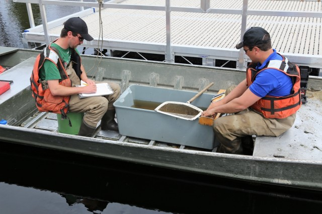 Watershed management biologists Derek Maki and Steve Rood with the Colorado State University conduct a fish survey at Swamp Pond on April 30, 2018, at Fort McCoy, Wis. The fish surveys, according to Fisheries Biologist John Noble with the Directorate of Public Works Environmental Division Natural Resources Branch, are necessary to determine the health of the installation's many waterways. The surveys produce data that is critical for fisheries management. Surveys include electrofishing streams and netting and electrofishing lakes and ponds, Noble said. Much care is taken to ensure the fish caught are not harmed. Fish caught include rainbow, brook, and brown trout; bluegills; bass; pumpkinseed; crappies; and other warm-water species. (U.S. Army Photo by Scott T. Sturkol, Public Affairs Office, Fort McCoy, Wis.)
