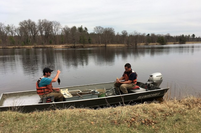 Watershed management biologists Derek Maki and Steve Rood with the Colorado State University conduct a fish survey at Swamp Pond on April 30, 2018, at Fort McCoy, Wis. The fish surveys, according to Fisheries Biologist John Noble with the Directorate of Public Works Environmental Division Natural Resources Branch, are necessary to determine the health of the installation's many waterways. The surveys produce data that is critical for fisheries management. Surveys include electrofishing streams and netting and electrofishing lakes and ponds, Noble said. Much care is taken to ensure the fish caught are not harmed. Fish caught include rainbow, brook, and brown trout; bluegills; bass; pumpkinseed; crappies; and other warm-water species. (U.S. Army Photo by Bill Coppernoll, Public Affairs Office, Fort McCoy, Wis.)