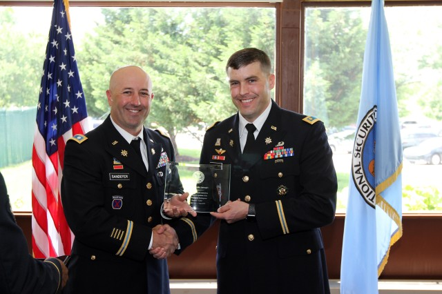 FORT GEORGE G. MEADE, Md. -- Maj. Brooks Jarnagin (right) receives a plaque from Lt. Col. Jesse Sandefer, the deputy commanding officer for the 780th Military Intelligence Brigade (Cyber), after graduating from the Army Intelligence Development Program -- Cyber (AIDP-Cyber) in a ceremony at the National Cryptologic Museum here on June 1.