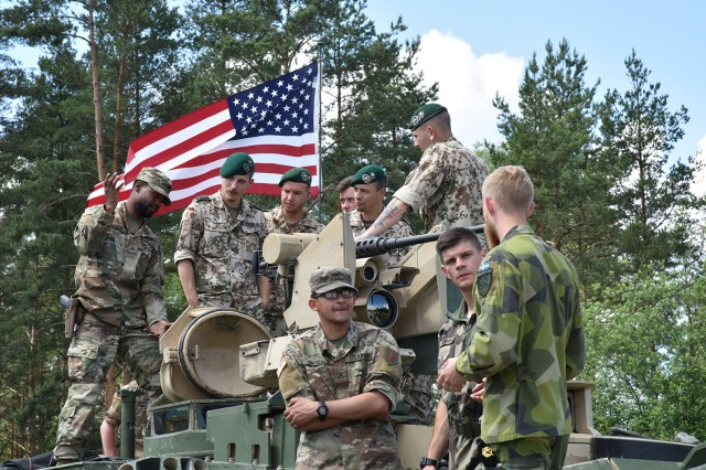 Tankers from France, Germany, Sweden and the U.S. talk to each other while checking out the competition's tanks during the Strong Europe Tank Challenge opening ceremony, held at 7th Army Training Command's Grafenwoehr Training Area, June 3, 2018.