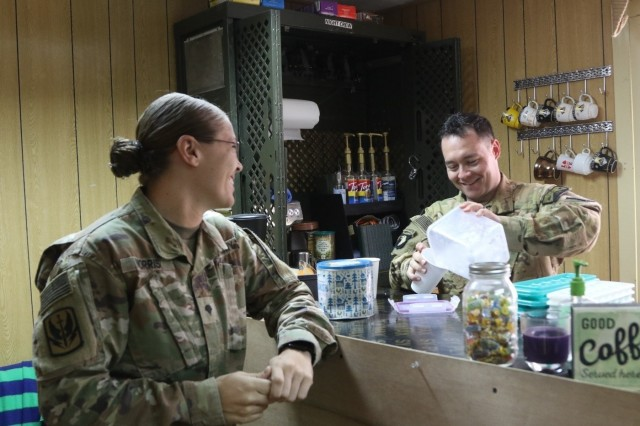 U.S. Army Chief Warrant Officer 2 Ryan Amato assigned to 1st Battalion, 189th Aviation Regiment, prepares an iced coffee for Spc Sarah Morris at the Dustoff Coffee shop at Camp Taji, Iraq May 18, 2018. The Dustoff Coffee shop is a donation-based business that provides funds for Soldiers in order to boost morale and build unit cohesion.