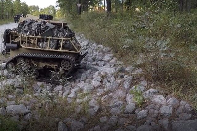 "The SMET system developed by Howe and Howe Technologies Inc. plows over rocks during the Phase I assessment in September. Among the four systems that are advancing to the Phase II assessment, it is the only tracked system. The goal of the SMET program is to provide infantry brigade combat teams (IBCTs) with a robotic ""mule"" capability."