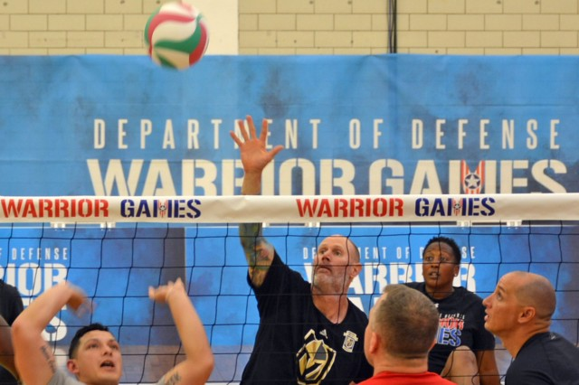 U.S. Army Ret. Capt. Steven Bortle, center, attempts to block a serve during seated volleyball practice, May 30, at the U.S. Air Force Academy, Colorado Springs, Colo. in preparation for the 2018 Department of Defense (DOD) Warrior Games, June 1 to June 9. During the 2018 Warrior Games approximately 250 athletes representing teams from the United States Army, Marine Corps, Navy/Coast Guard, Air Force, and Special Operations Command, as well as athletes from international partner nations, the United Kingdom Armed Forces, the Australian Defence Force, and the Canadian Armed Forces, will participate in 10 sporting events: archery, cycling, powerlifting, sitting volleyball, shooting, swimming, wheelchair basketball, track and field, and new this year,  powerlifting and indoor rowing. Participants include athletes with upper-body, lower-body and spinal cord injuries; amputations; serious illnesses; traumatic brain injuries; visual impairment and post-traumatic stress disorder. The Warrior Games highlight the resiliency and strength of our service members, veterans and their caregivers. (U.S. Army photo by Leanne Thomas)