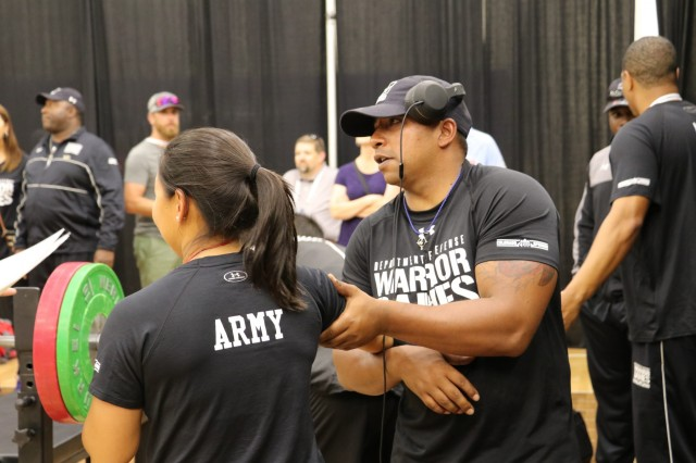 U.S. Army Sgt. 1st Julio Rodriguez helps Sgt. 1st Class Hyoshin Cha loosen up her shoulder before the powerlifting competition June 5, 2018, in the U.S. Air Force Academy's Cadet Gymnasium at the 2018 Department of Defense Warrior Games. The DoD Warrior Games are conducted from June 2 - 9. It is an adaptive sports competition for wounded, ill and injured service members and veterans. Approximately 300 athletes representing teams from the Army, Marine Corps, Navy, Air Force, Special Operations Command, United Kingdom Armed Forces, Canadian Armed Forces, and the Australian Defence Force will compete in archery, cycling, track, field, shooting, sitting volleyball, swimming, wheelchair basketball, and - new this year - powerlifting and indoor rowing. (U.S. Army photo by Robert Whetstone)