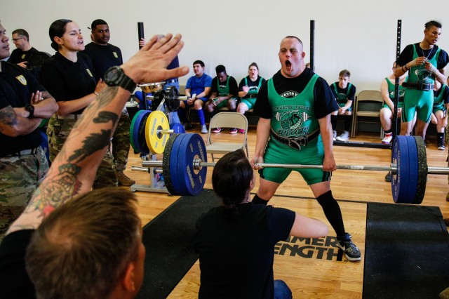 Volunteers from 1st Special Forces Group (Airborne) encourage a Special Olympics athlete during his deadlift event at Evergreen Theater on Joint Base Lewis-McChord during the Washington State Special Olympics Powerlifting event, June 2. The volunteers from the 4th Battalion, 1st SFG (A) helped set up the event and acted as judges, coaches and mentors.