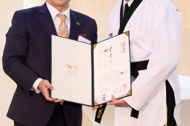 Lt. Gen. Michael A. Bills, Eighth Army commanding general, receives taekwondo uniform with black belt level six, and certificate from Oh, Hyun-deuk, president of Kukkiwon, the World Taekwondo Headquarters at the Army Convention Center, Yongsan, South Korea, June 5.