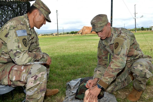 Cpl. Harley Young (right) gives a demonstration on inserting a nasopharyngeal airway tube as Sgt. 1st Class Adam Daponte keeps time during Expert Infantryman Badge train up at Schofield Barracks, Hawaii, on June 6, 2018.  Both Soldiers are infantrymen assigned to 2nd Battalion, 27th Infantry Regiment, 3rd Brigade Combat Team, 25th Infantry Division. Infantrymen throughout the 25th ID are participating in this biannual event to earn the prestigious Expert Infantryman Badge. (U.S. Army photo by Staff Sgt. Armando R. Limon, 3rd Brigade Combat Team, 25th Infantry Division)