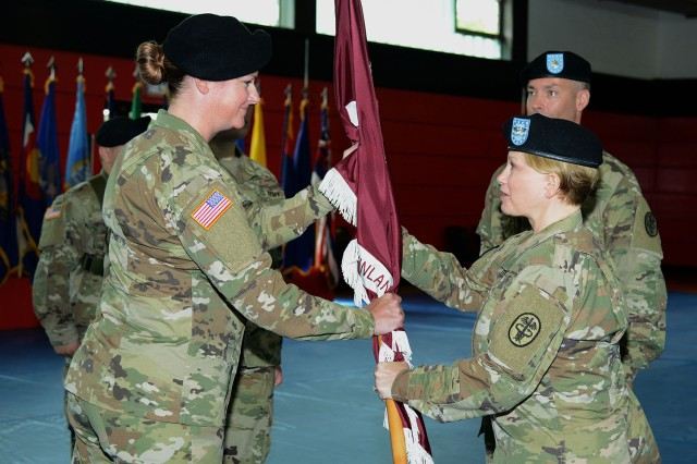 Lt. Col. Brianna M. Perata, incoming Public Health Activity - Rheinland Pfalz commander, left, accepts the unit colors from Public Health Command Europe commander Col.  Rebecca I. Porter during the PHA-RP change of command ceremony June 1. Perata took command from Lt. Col Kenneth D. Spicer, far right.