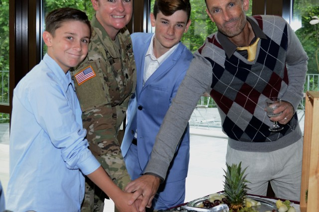 Lt. Col. Brianna M. Perata, new Public Health Activity - Rheinland Pfalz commander, her husband, Matt Perata, and sons, Jackson, 14, and Beckham, 12, cut the cake during a reception following the PHA-RP change of command ceremony June 1 at the Landstuhl Fitness Center.