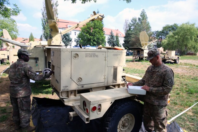 U.S. Army Spc. Javon Ferguson (left) and U.S. Army Spc. Logan Fennecken, both assigned to Bravo Company, 151st Expeditionary Signal Battalion, 228th Theater Tactical Signal Brigade, perform generator maintenance to prepare their equipment to go on mission, June 5, 2018, in Boleslawiec, Poland.