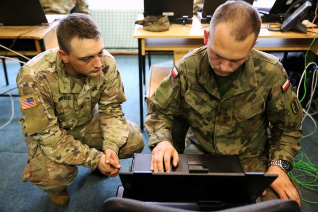U.S. Army Spc. Chene Nowicki, assigned to Alpha Company, 44th Expeditionary Signal Battalion, 2nd Theater Signal Brigade, and Polish Army Capt. Greg Zendelek, assigned to the 12th Mechanized Division G-6 section, set up a computer during exercise Saber Strike, June 2, 2018 in the Drawsko Pomorskie Training Area, Poland.