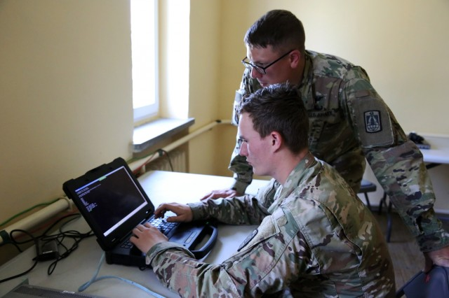U.S. Army Spc. Erik Lundquist (at keyboard) and Sgt. Michael Cole, both assigned to Bravo Company, 86th Expeditionary Signal Battalion, 11th Theater Tactical Signal Brigade, troubleshoot a switch at the company forward NETOPS during exercise Saber Strike, June 4, 2018 near Powidz, Poland. Saber Strike is a U.S. Army Europe-led exercise involving approximately 18,000 Soldiers from 19 participating nations taking place in Lithuania, Estonia, Latvia and Poland from June 3-15, 2018.