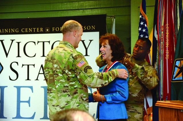 Fort Jackson Commander Maj. Gen Pete Johnson and Post Command Sgt. Maj. Lamont Christian present Susan McPherson with the Fort Jackson Hall of Fame Medalion, during the 5th annual Hall of Fame Induction ceremony held at the Fort Jackson NCO Club June 1.