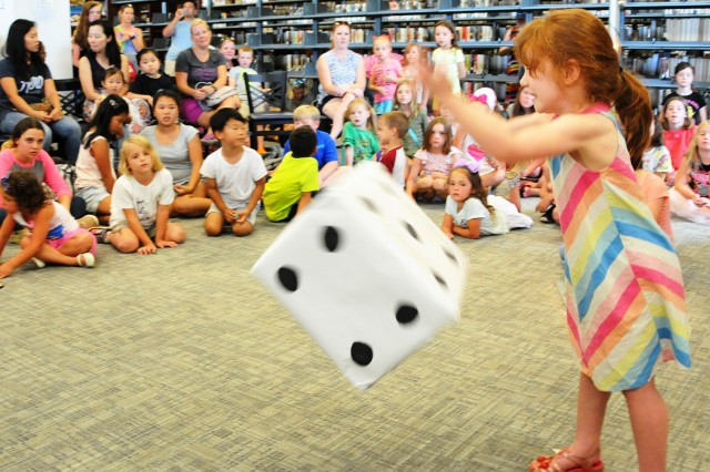 Eliana Fell, military family member, throws a die during the Dice Game of the Center Library's 'The Price Is Right' game show at the kickoff party.
