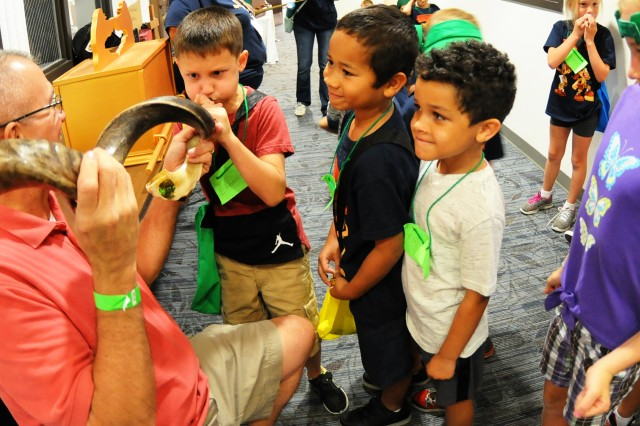 Children take turns blowing into a horn to make noise at a previous Vacation Bible School at the Spiritual Life Center.