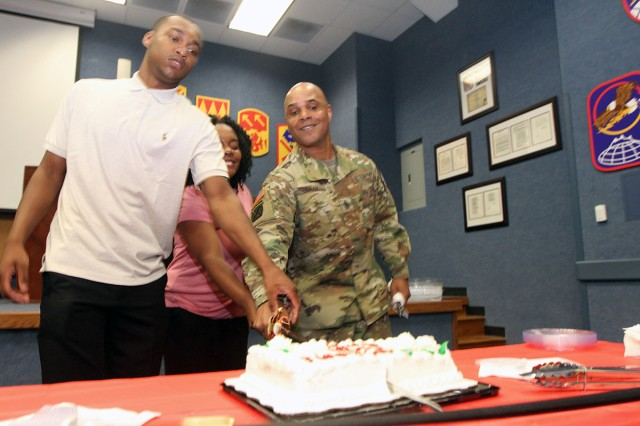 Command Sgt. Maj. Randy Gray, 30th ADA Brigade CSM, cuts a cake with his children Earl, and Randi, June 4, at a reception welcoming them to the Lawton-Fort Sill community.