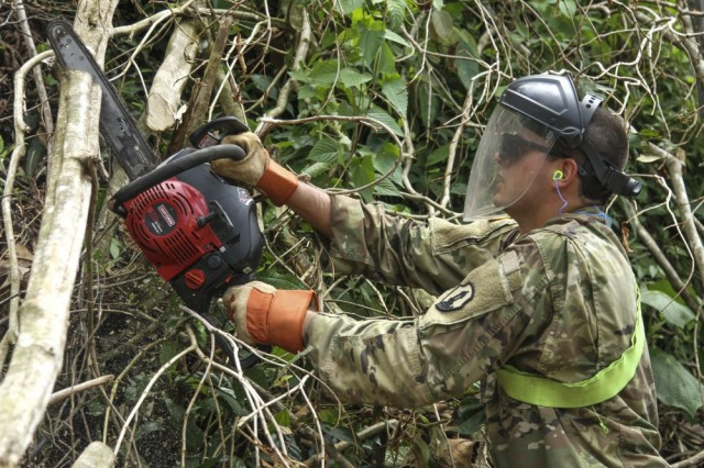 A Soldiers from the U.S. Army Reserve - Puerto Rico clears a road in the mountains of Puerto Rico, in the aftermath of Hurricane Maria, 2017.
