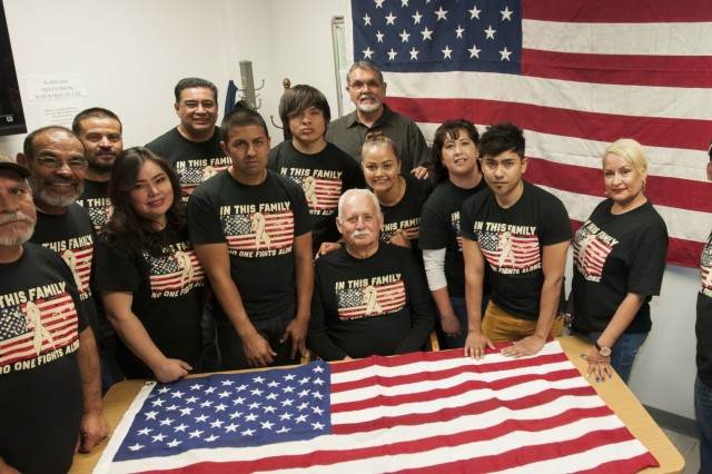 "Ramon Gomez (sitting and center), a quality assurance evaluator, Environmental Services, Logistics Division, William Beaumont Army Medical Center, is surrounded by coworkers wearing shirts that display their support for Gomez, who was diagnosed with stage IV lung cancer in 2016. The self-proclaimed ""tight-knit group"" publicly supports Gomez's fight with cancer with wear of their shirts each Friday, among other initiatives to assist Gomez during his cancer treatment."