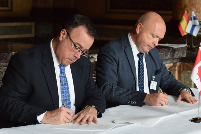 Brig. Gen. Michael Rafter of Canada, left, and Maj. Gen. Thierry Dupont of Belgium, the current chair of the National Territorial Commanders' Committee, sign the memorandums officially inducting Canada into the NTCC June 6 in Brussels, Belgium. The newest members - Canada, Finland and Spain - grow the NTCC ranks to 29 strong.