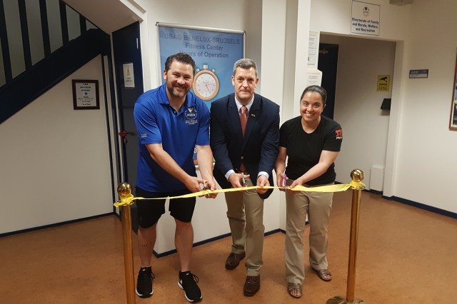 The Brussels Fitness Center marked 24/7 access with a ribbon-cutting ceremony joined by Raymond Myers (center), deputy garrison manager for Brussels, and Command Sgt. Maj. Samara Pitre (right), command sergeant major for U.S. Army Garrison Benelux, May 31, 2018, in Brussels, Belgium.