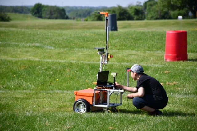 A robotics student double-checks systems on his autonomous vehicle during the Intelligent Ground Vehicle Competition June 4, 2018, at Oakland University, Auburn Hills, Michigan.  The IGVC, co-hosted by U.S. Army TARDEC, brings together students from around the world to build and test fully-autonomous ground vehicles around a course, navigating waypoints and obstacles in the fastest time possible. [U.S. Army Photo by Douglas Halleaux/Released]