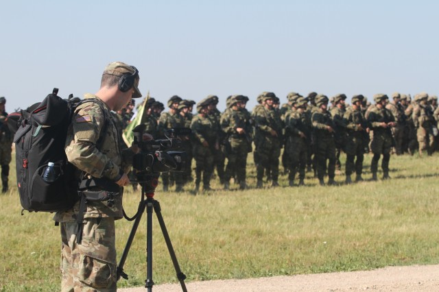 Spc. Steven Selis of the Michigan Army National Guard, 126th Press Camp Headquarters, records the opening ceremony of Saber Strike 18 at the Bemowo Piskie Training Area in Poland on June 4, 2018. Saber Strike 18 is the eighth iteration of the long-standing U.S. Army Europe-led cooperative training exercise designed to enhance interoperability among allies and regional partners.