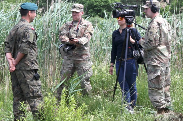 Soldiers from the Michigan Army National Guard, 126th Press Camp Headquarters, interview an engineer specialist from Poland's 15th Mechanized Brigade about the wet bridge crossing exercise taking place during Saber Strike 18 in Ruda, Poland on June 5, 2018. Saber Strike 18 is the eighth iteration of the long-standing U.S. Army Europe-led cooperative training exercise designed to enhance interoperability among allies and regional partners.