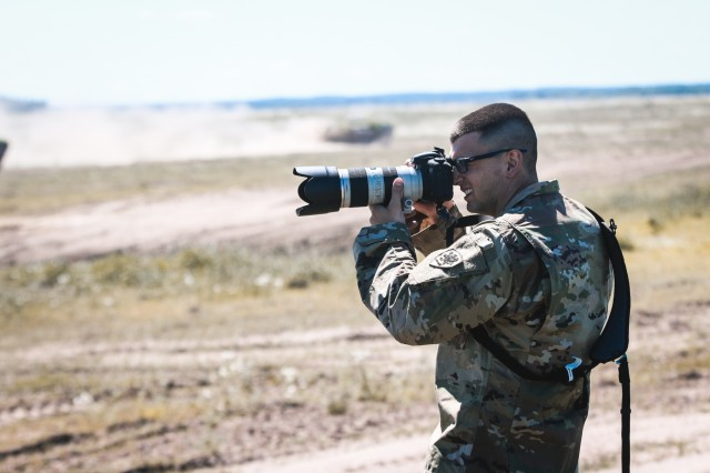 Spc. Alan Prince, public affairs specialist with the 126th Press Camp Headquarters, Michigan Army National Guard, takes a photograph of a military training event during Saber Strike 18 with Battle Group Poland at Bemowo Piskie Training Area, Poland on June 7, 2018.